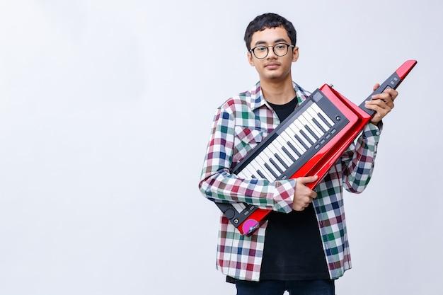 Portret strzał przystojny młody nastoletni muzyk grający na keytar patrząc w kamerę w studio. młody młodszy muzyk stojący i trzymający keytar na białym tle