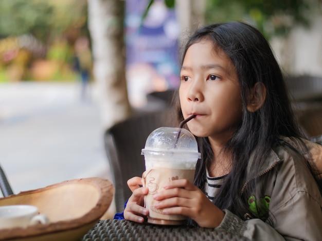 Portret strzelał mała azjatycka dziewczyna pije czekoladowego mleko