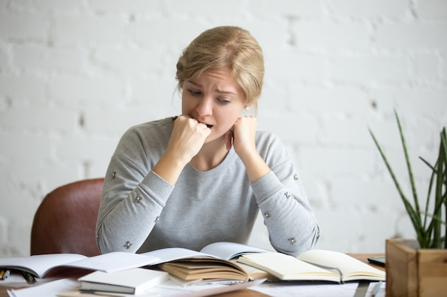 Portret studenta dziewczyna siedzi przy biurku odgryzaniem pięść
