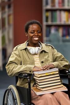 Portret studenta na wózku inwalidzkim w bibliotece