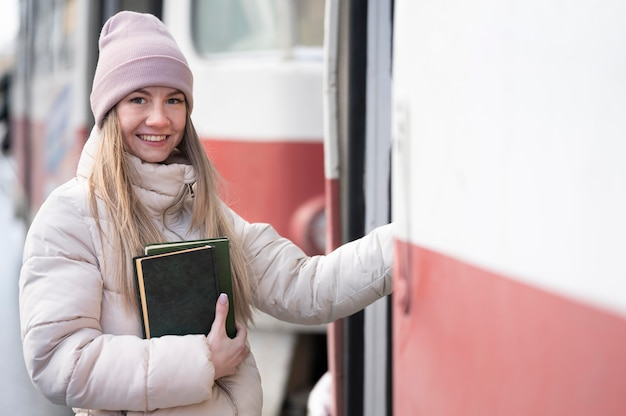 Portret studentka z książkami na przystanku tramwajowym