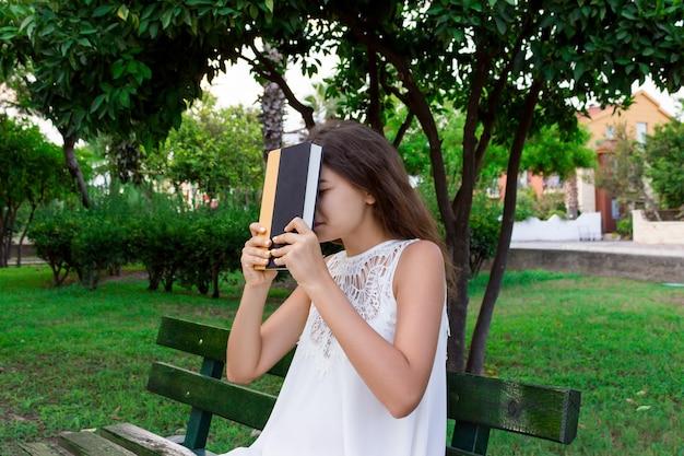 Portret studentki, która jest zmęczona studiowaniem, siedzi na ławce na zewnątrz i trzyma książkę.