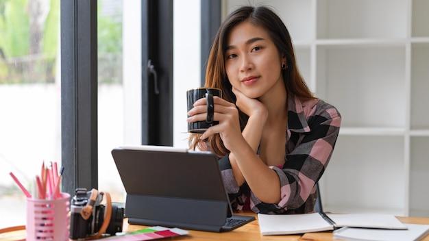 Portret studentki uśmiecha się do kamery podczas picia kawy podczas wykonywania zadania w salonie