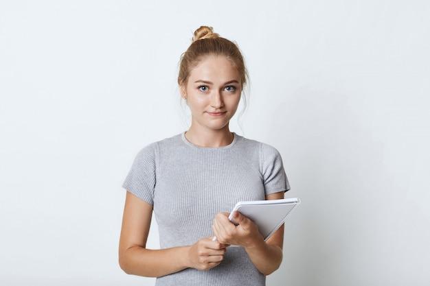 Portret studentki z jasnymi włosami kok, ubrany od niechcenia, utrzymujący notatnik w ręce, idę pisać notatki z wykładu, odizolowane na białej ścianie. kobieta z pozycjonowanie portfel