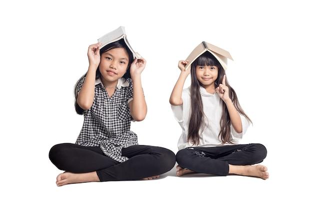 Portret studentów azjatyckich dzieci siedzi na białym tle