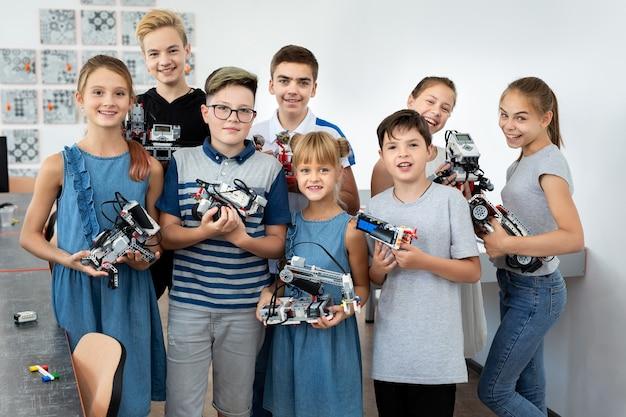 Portret studentów płci męskiej i żeńskiej budujący pojazd robota w klasie kodowania komputera po szkole