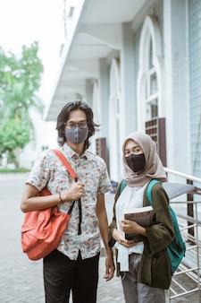 Portret studentów w maskach, patrząc od frontu na dziedzińcu kampusu.