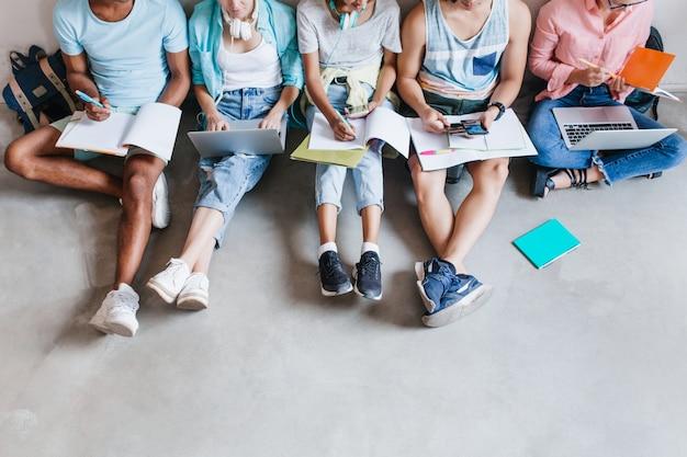 Portret studentów w modnych trampkach, schładzających się na podłodze, przygotowujących się do wspólnych egzaminów. przyjaciele z uniwersytetu spędzają razem czas przy laptopach i pisząc streszczenie.