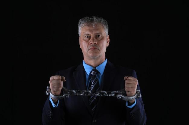 Portret studyjny biznesmena w kajdankach