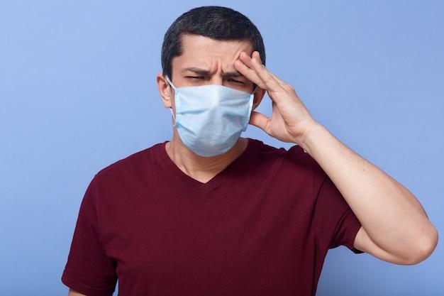 Portret studyjny chorej brunetki o zmarszczonej twarzy, z bólem głowy, zamykaniem oczu, maską medyczną, palcami na czole, gorączką, infekcją, osłabieniem.