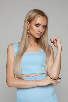 Portret studyjny fotografii pięknej kaukaskiej blondynki z długimi prostymi włosami na sobie biżuterię