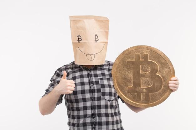 Portret studyjny mężczyzn w wesołej papierowej masce pokazujący kciuk w górę z dużym bitcoinem