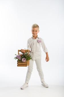 Portret studyjny modnego blond kaukaskiego chłopca z drewnianym koszem kwiatów