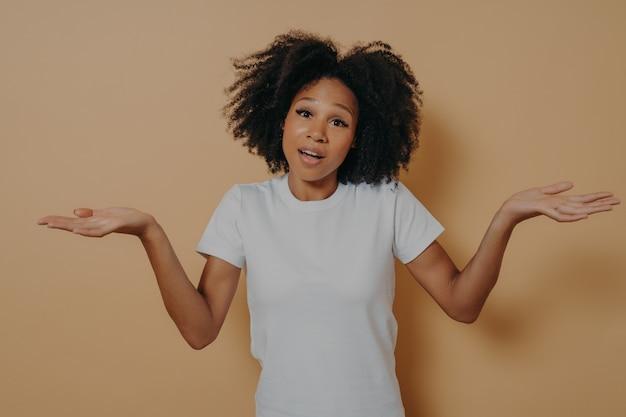 Portret studyjny niepewnej kobiety o ciemnej skórze, wzruszając ramionami i rozkładając ręce na boki, nie może udzielić odpowiedzi na pytanie lub mając wątpliwości, stojąc na białym tle na beżowym tle