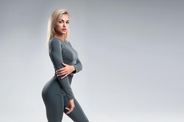 Portret studyjny pięknej dziewczyny o sportowej sylwetce w legginsach i bluzce na szarym tle