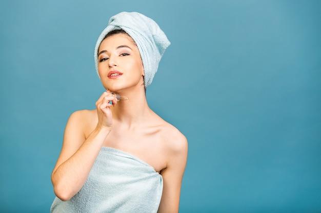 Portret studyjny przeznaczone do walki radioelektronicznej z młoda kobieta w ręcznik na głowie na białym tle na przestrzeni kopii stosując serum olejowe z pipety.