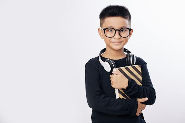 Portret studyjny uśmiechniętego chłopca preteen azjatyckich w okularach stojących z książką i słuchawkami