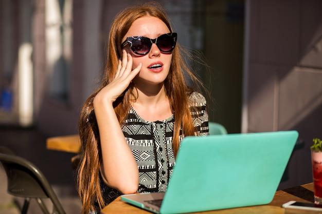 Portret styl życia całkiem studentka ruda dziewczyna, siedząc na tarasie kawiarni, używając swojego laptopa