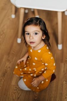 Portret styl życia malucha dziewczyna w żółtej musztardowej sukience na podłodze w domu. . wysokiej jakości zdjęcie