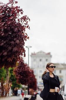Portret styl życia na zewnątrz wspaniałej brunetki dziewczyny. picie kawy i spacerowanie ulicą miasta.