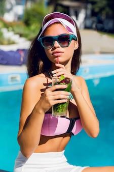 Portret styl życia opalonej pięknej kobiety w różowym bikini i okularach przeciwsłonecznych, siedząc w pobliżu basenu ze świeżym koktajlem.
