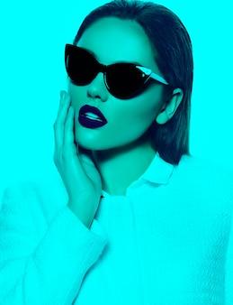 Portret stylowa piękna młoda kobieta z okularami przeciwsłonecznymi w turkusie