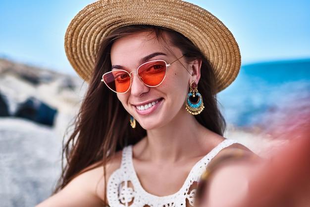 Portret stylowa piękna uśmiechnięta lato kobieta w słomianym kapeluszu i czerwonych szkłach