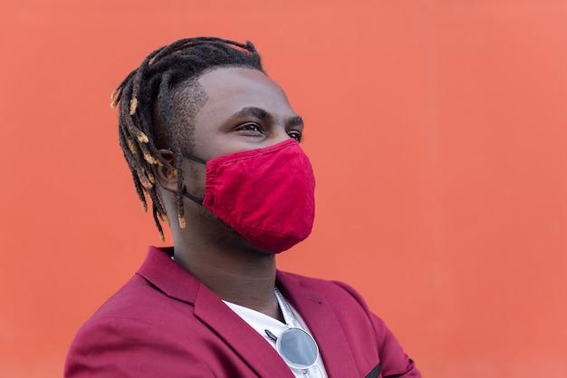 Portret stylowego afrykańskiego mężczyzny w masce ochronnej pasującej do garnituru na czerwonym tle