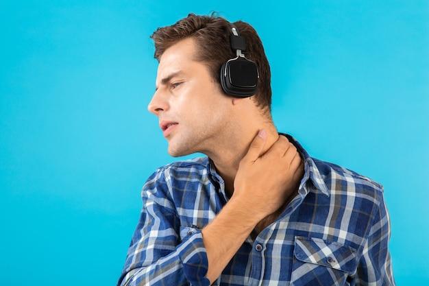 Portret stylowego atrakcyjnego przystojnego młodego mężczyzny słuchającego muzyki na słuchawkach bezprzewodowych