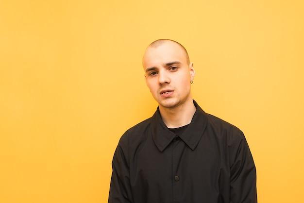Portret stylowego chłopca w czarnej kurtce na żółtym tle i patrzy w kamerę.