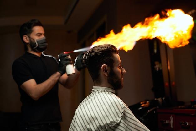 Portret stylowego klienta brodatego mężczyzny siedzącego na krześle i czekającego, podczas gdy biegły fryzjer przygotowuje się do strzyżenia z ogniem. koncepcja usługi ekstremalnej męskości w zakładzie fryzjerskim