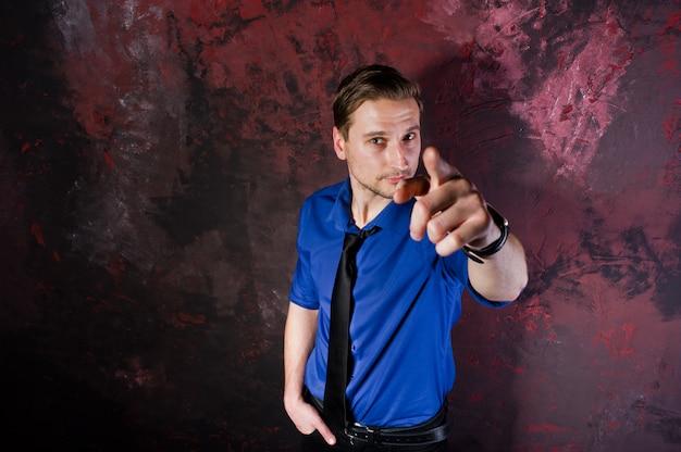 Portret stylowego mężczyzny, nosić na niebieskiej koszuli i krawacie, pokazując palcem.