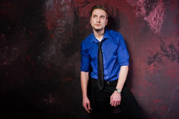 Portret stylowego mężczyzny, nosić na niebieskiej koszuli i krawacie.