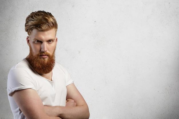 Portret stylowego rudowłosego hipster z rozmytą brodą, ubrany w białą koszulkę z podwiniętymi rękawami, pozuje w pomieszczeniu ze skrzyżowanymi rękami, z ponurym wyrazem twarzy.