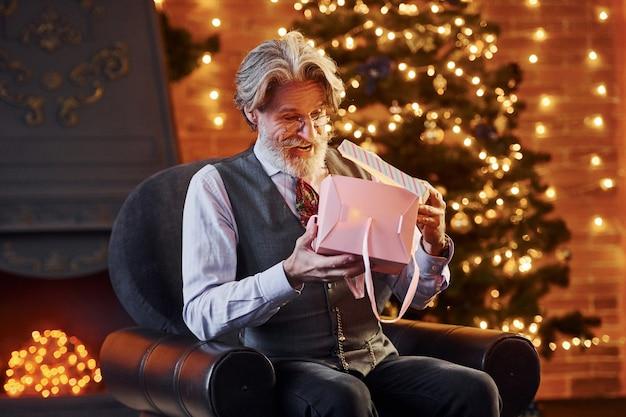 Portret stylowego seniora z siwymi włosami i brodą znajduje się w udekorowanej bożonarodzeniowej izbie z pudełkiem prezentowym.