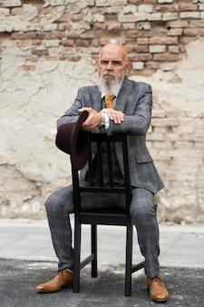 Portret stylowego starszego mężczyzny siedzącego na zewnątrz