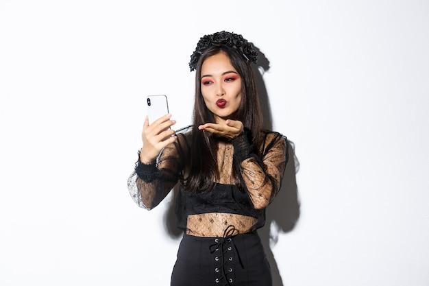 Portret stylowej azjatyckiej blogerki z gotyckim makijażem i kostiumem na halloween, wysyłającej pocałunek w aparacie telefonu komórkowego, nagrywającej wideo lub prowadzącej rozmowę wideo, stojąc na białym tle.