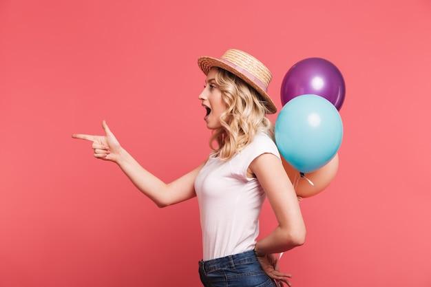 Portret stylowej blond kobiety w słomkowym kapeluszu uśmiecha się, trzymając kilka kolorowych balonów odizolowanych nad różową ścianą