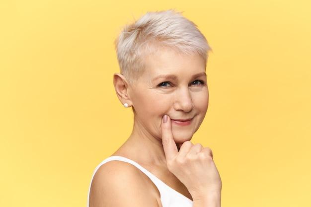 Portret stylowej blondynki dojrzałej kobiety w podkoszulku bez rękawów, zwężonych oczu, patrzącej z zamyślonym, tajemniczym uśmiechem, trzymającej palec na policzku, rozmyślającej nad pomysłem