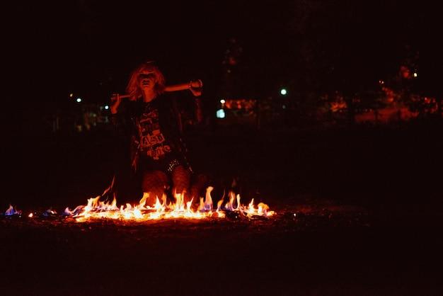 Portret stylowej blondynki grunge młodej kobiety z klubem przy ogniu