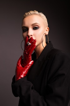 Portret stylowej blondynki z czerwonymi skórzanymi rękawiczkami
