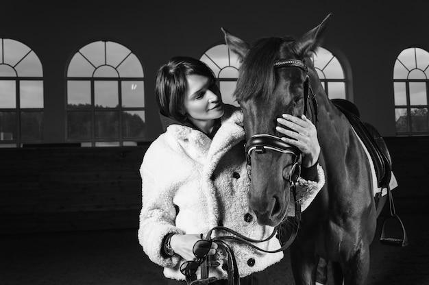 Portret stylowej kobiety przytula konia pełnej krwi. koncepcja miłości i opieki. różne środki przekazu