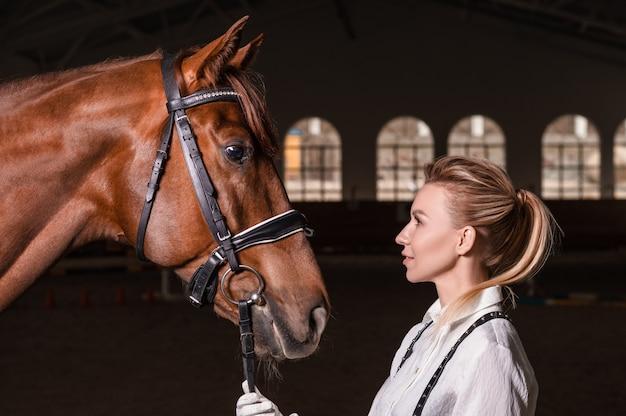 Portret stylowej kobiety przytulanie konia pełnej krwi. koncepcja miłości i opieki. różne środki przekazu