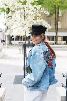 Portret stylowej kobiety ubranej w dżinsową kurtkę i czarną czapkę