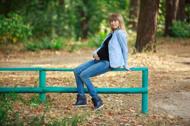 Portret stylowej kobiety w ciąży spacery w dżinsach w parku jesień. szczęśliwa blondynki kobieta w ciąży dotyka brzucha na naturze w słoneczny dzień. 9 miesięcy zdrowej ciąży. kobieta czeka na poród