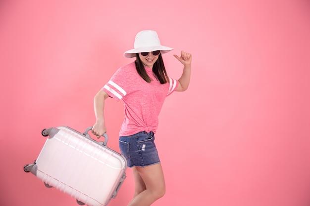 Portret stylowej kobiety w modnych letnich ubraniach i białym kapeluszu na różowo z walizką do podróży.