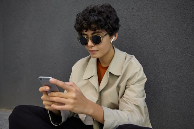 Portret stylowej ładnej brunetki z kręconymi, krótkimi włosami w okularach przeciwsłonecznych i słuchawkach, pozując nad betonową czarną ścianą, trzymając smartfon w rękach i patrząc na ekran ze spokojną twarzą