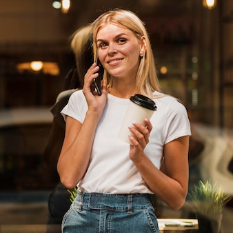 Portret stylowej młodej kobiety rozmawia przez telefon