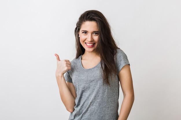 Portret stylowej młodej ładnej kobiety uśmiechając się w szary t-shirt na na białym tle, pokazując kciuk do góry, szczęśliwy, pozytywny gest