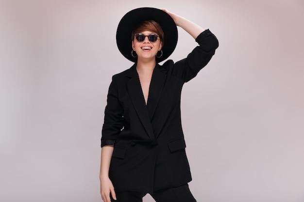 Portret stylowej pani w okularach przeciwsłonecznych i kapeluszu z szerokim rondem. fajna młoda kobieta w czarnej kurtce i spodniach pozuje i uśmiecha się na na białym tle